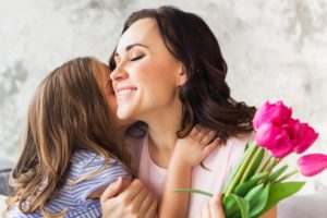 Mother and Little girl embrace over Mother's Day Bouquet.